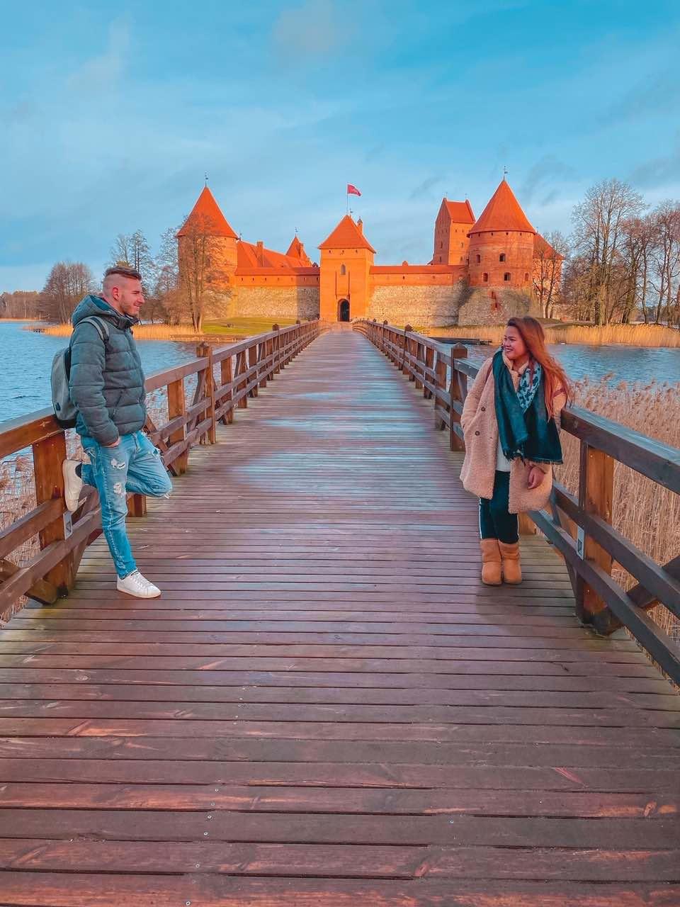 coppia di ragazzi sorridono sul ponte del castello di Trakai in Lituania