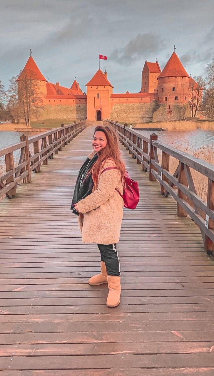 ragazza felice sul ponte del castello di Trakai in Lituania
