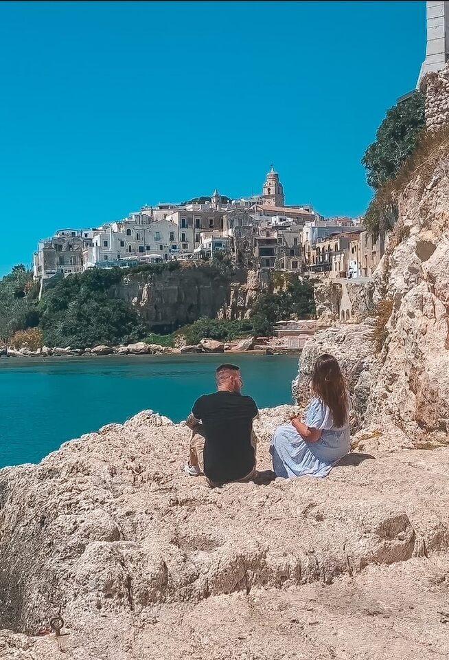 Coppia seduta su una roccia ammira il panorama sul centro storico di Vieste