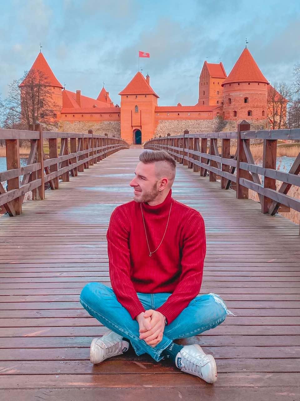 ragazzo sorride seduto sul ponte del bellissimo castello di Trakai in Lituania