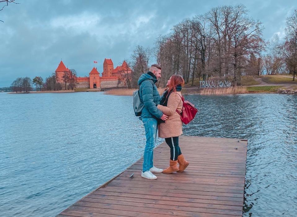 coppia si abbraccia davanti al castello di Trakai in Lituania