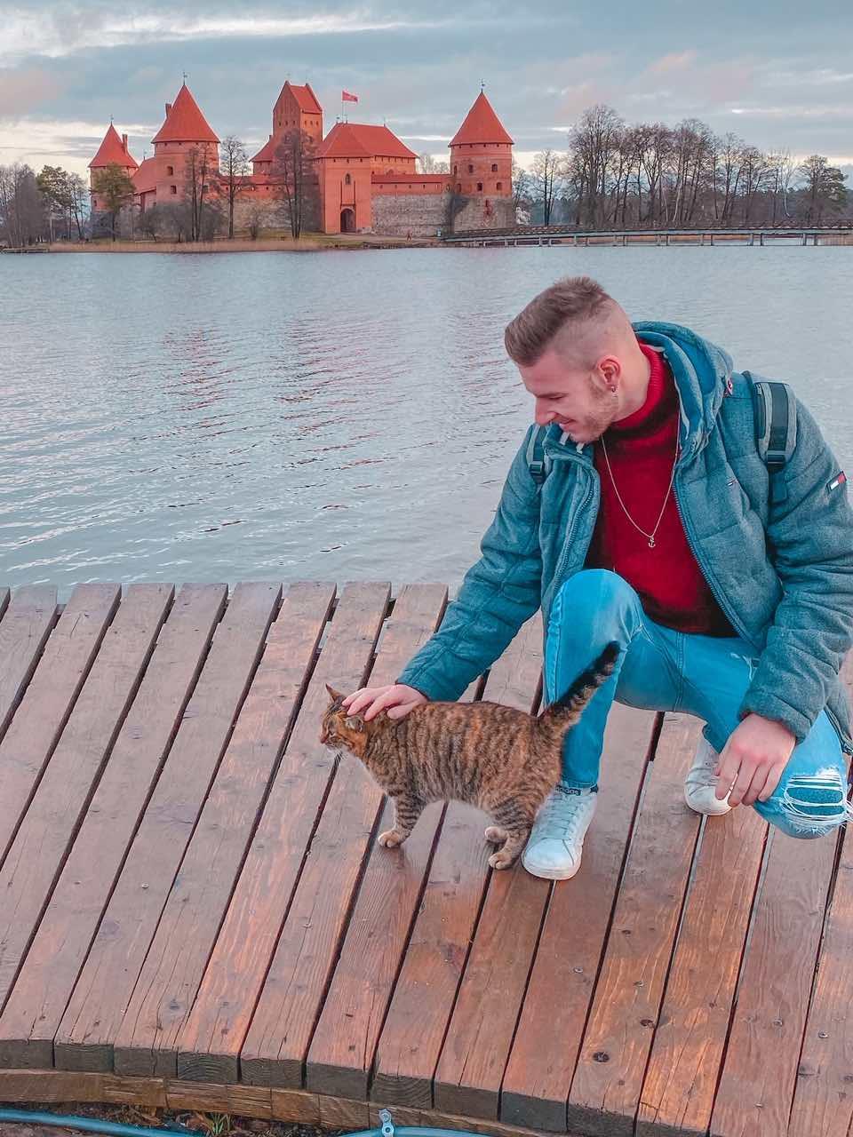 ragazzo che accarezza un gatto sul pontile che si affaccia sul lago intorno al castello di Trakai in Lituania