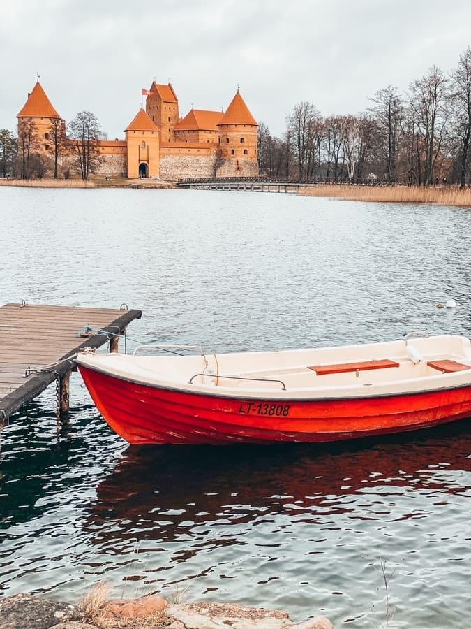 barca galleggia sul lago che circonda il castello di Trakai sullo sfondo