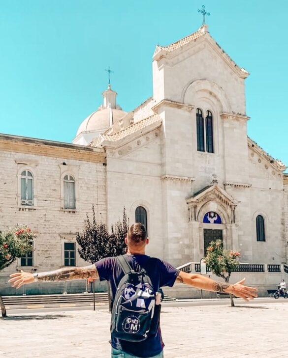 Ragazzo davanti alla bellissima chiesa di San Domenico nella Piazza Vittorio Emanuele II di Giovinazzo