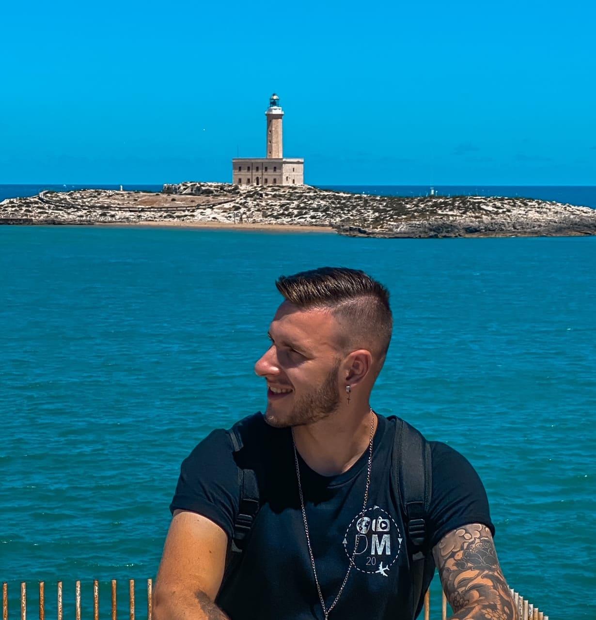Ragazzo sorride guardando la vista panoramica sul faro e mare di Vieste