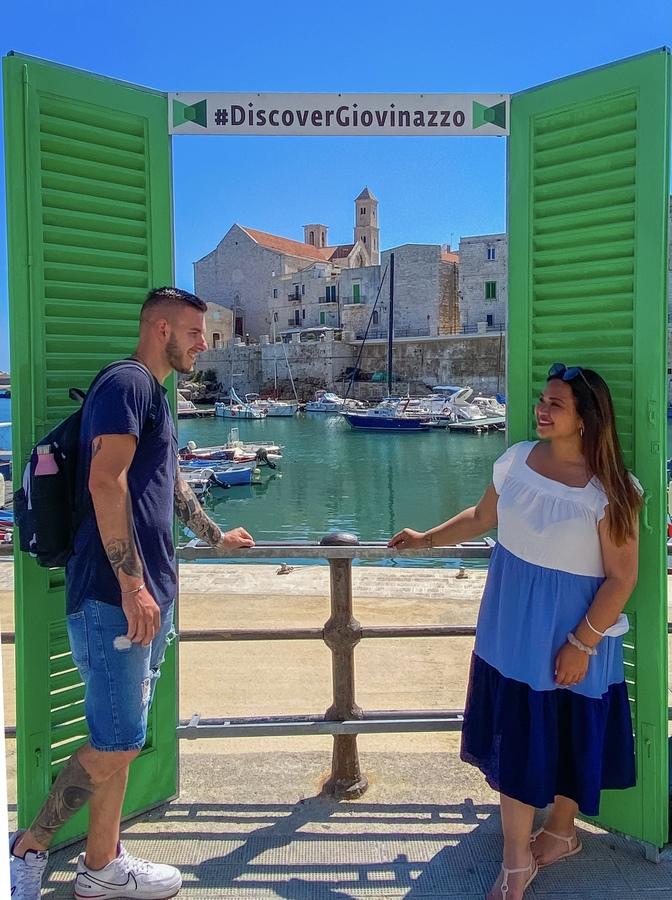coppia sorride davanti alla finestra verde con vista panoramica sul mare e porto di Giovinazzo
