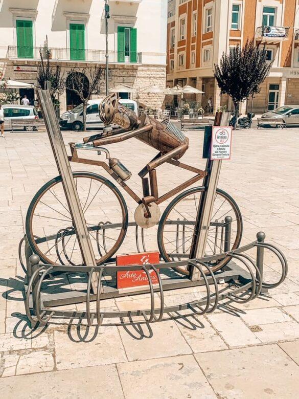 scultura di ciclista portabici nella Piazza Vittorio Emanuele II di Giovinazzo