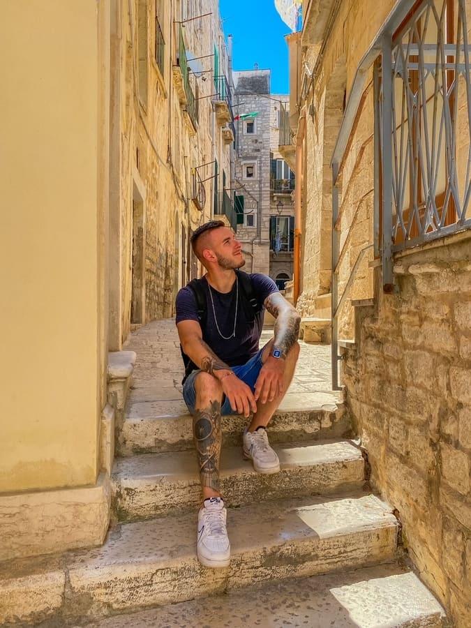 ragazzo seduto sulle scalinate di un bellissimo vicolo instagrammabile di Giovinazzo