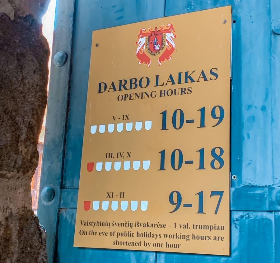 cartello con orari per visitare il castello di Trakai in Lituania