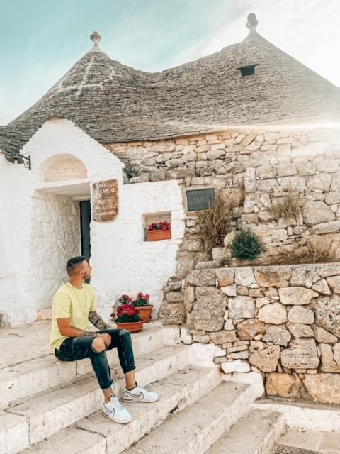 Ragazzo seduto davanti ai trulli siamesi da vedere ad Alberobello